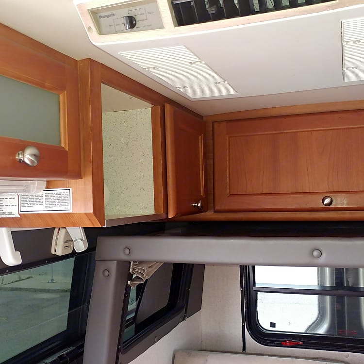 View to Rear with Slide Retracted Ready for Driving - Showing Roof Mounted A/C and Storage Spaces Above Slide and Above Counter Top.