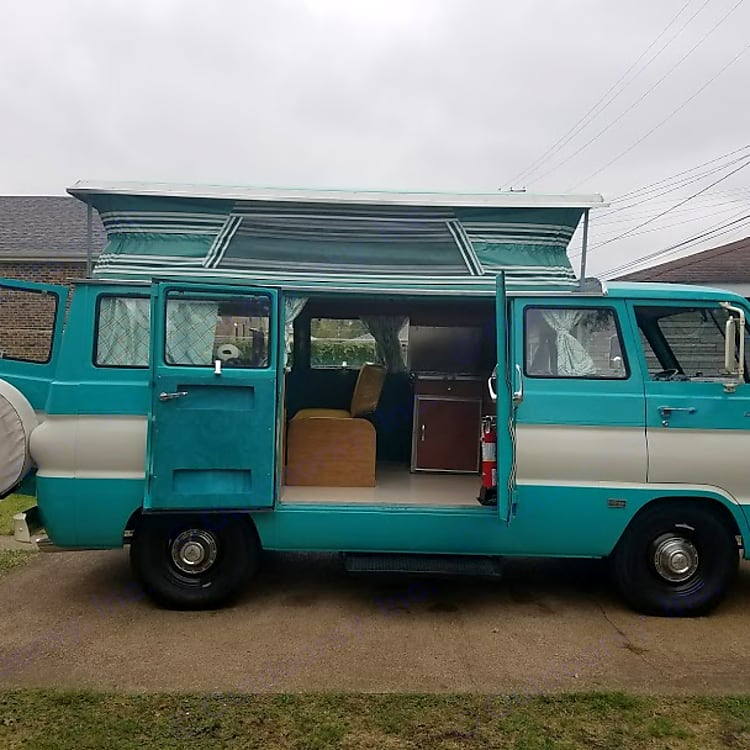 The side of the CampWagon with the doors open, the poptop up and the mechanically operated step engaged.