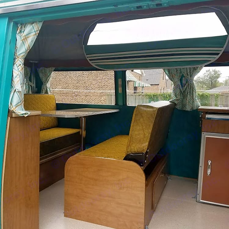 The camper interior of the CampWagn with the dinette table set up and the screened vent windows unzipped.