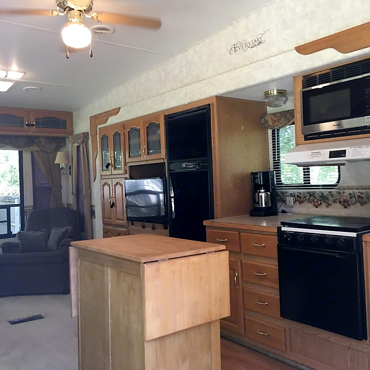 Tall lounge area, 2 slides, new fireplace, large refrigerator wth full freezer, movable island, gas cooktop, micro, full oven, his and hers recliners , huge picture window.