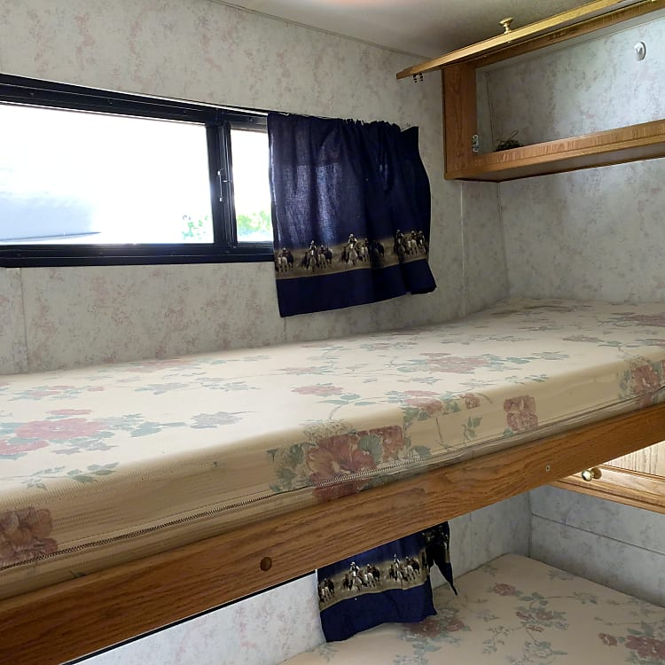 The single over single bunk beds are in their own cozy bedroom.  Each bed has it's own convenient storage cupboard.  This area is partitioned off by a curtain.
