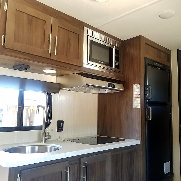 Stainless steel sink, two burner stove, microwave, refrigerator and freezer