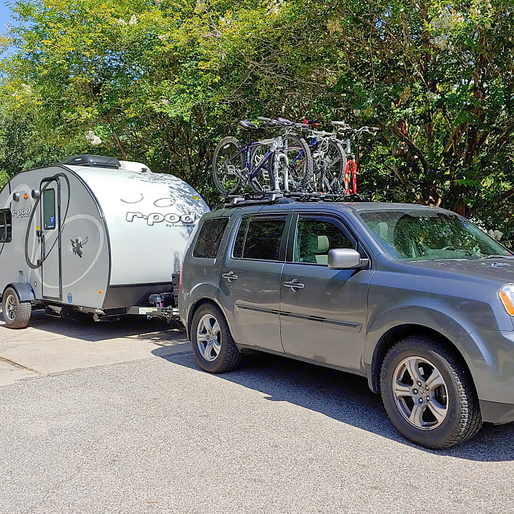 The pod on the go!  As a family of 4, we put 3 bikes on our car and one inside on a bunk.  The other side has a handy outdoor shower.