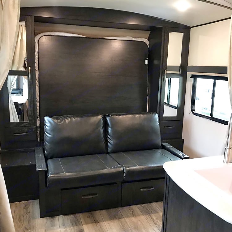 A leather sofa is easily set up once the Murphy bed is stowed up. The sofa can be laid down if needed for a quick day bed nap! That's one of our favorite things about this camper is how easily it can be customized for your needs! Closet space is available on both sides of the sofa and two spacious drawers are located underneath.