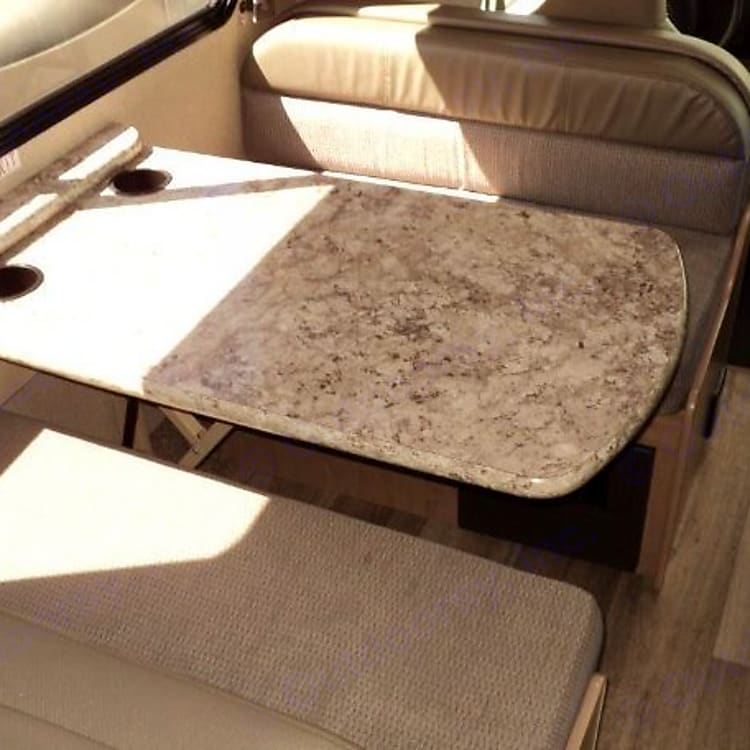 Dinette lays flat to accommodate a smaller person or child. Contains 2 seatbelts on each side. Easy pull down shade.