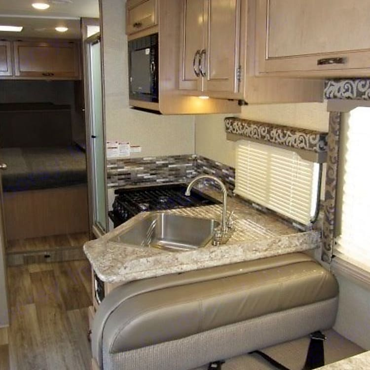 Modern kitchen with updated counter, cabinet and trim colors.  Stainless sink, microwave, gas-3 burner stove and oven.