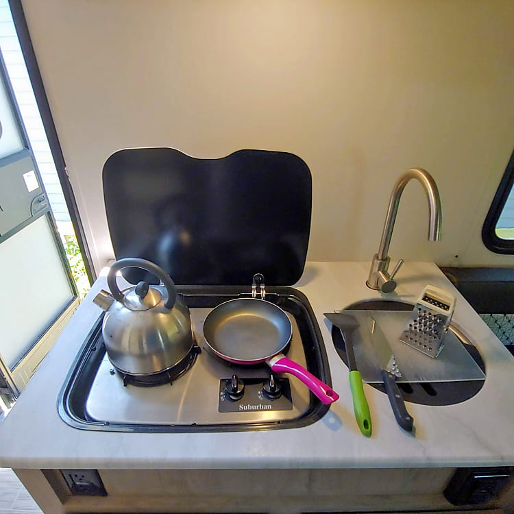 Two burner cook top and sink/counter area are perfect for preparing a meal or for prepping to cook outside on the grill.