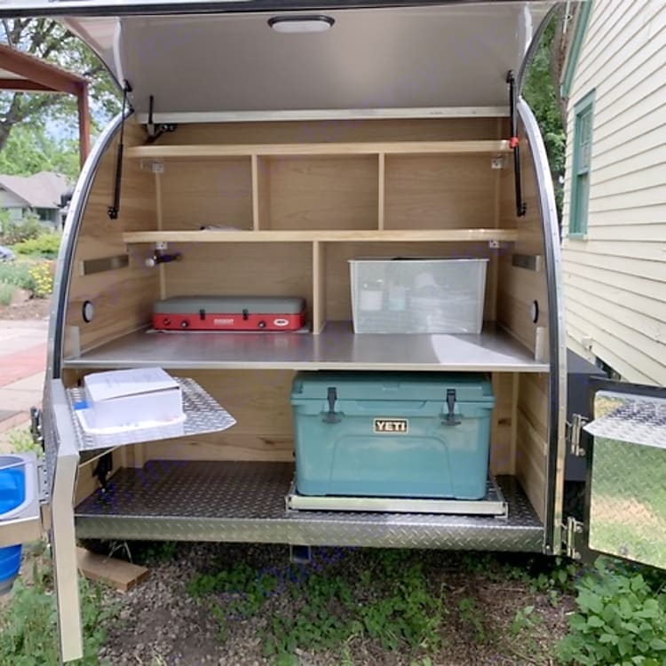 rear galley w cooler, stove, kitchen supplies, sink, pop up tables on doors