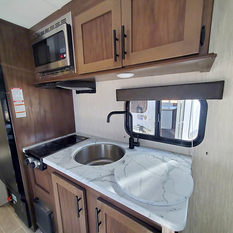 Large stainless steel sink and two burner gas stove with microhood.