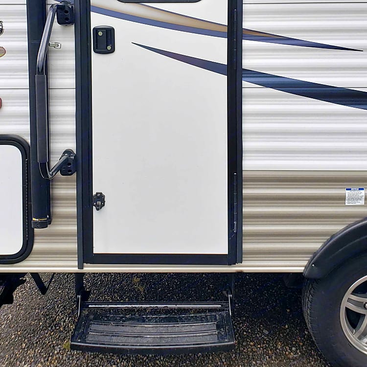 Passenger side of the trailer with rear entry door, access swing out handle, and pull out step.