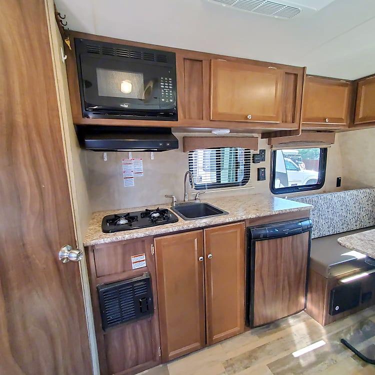 Kitchen with 2 burner stove, hood/microwave, sink, and fridge.