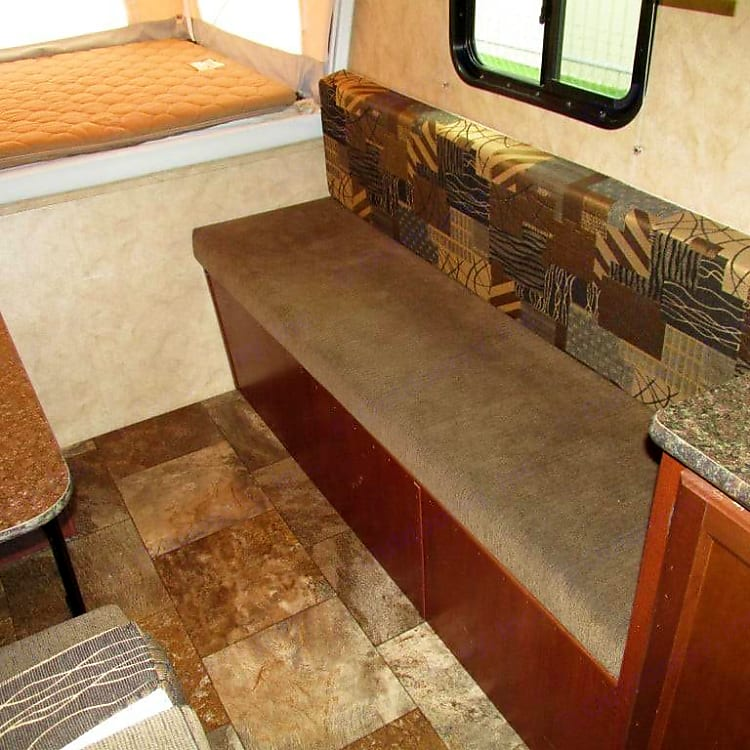 Additional bench seating with storage bin underneath, which is accessible outside.