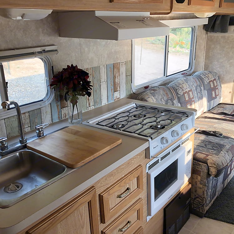 Double sided sink with extra counter space wood sink insert over.  High spout faucet.  Three burner gas range with a microwave below.