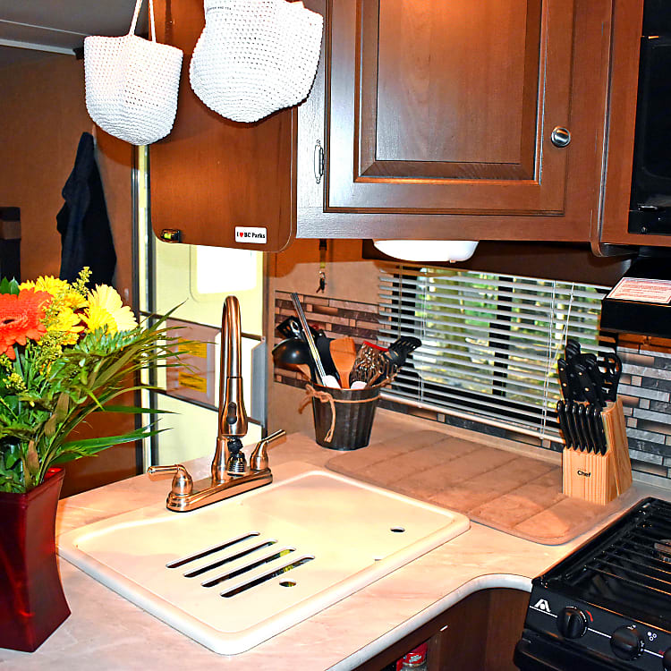 Full kitchen with large sink, 3 burner stove, microwave, small oven, mid-size fridge an freezer