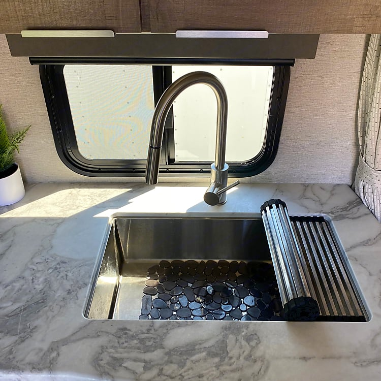 Deep seated stainless steel kitchen sink with roll up drying mat.
