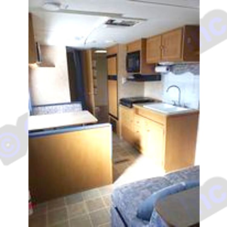 View of kitchen sink, stove top, microwave, refrigerator, and dining table