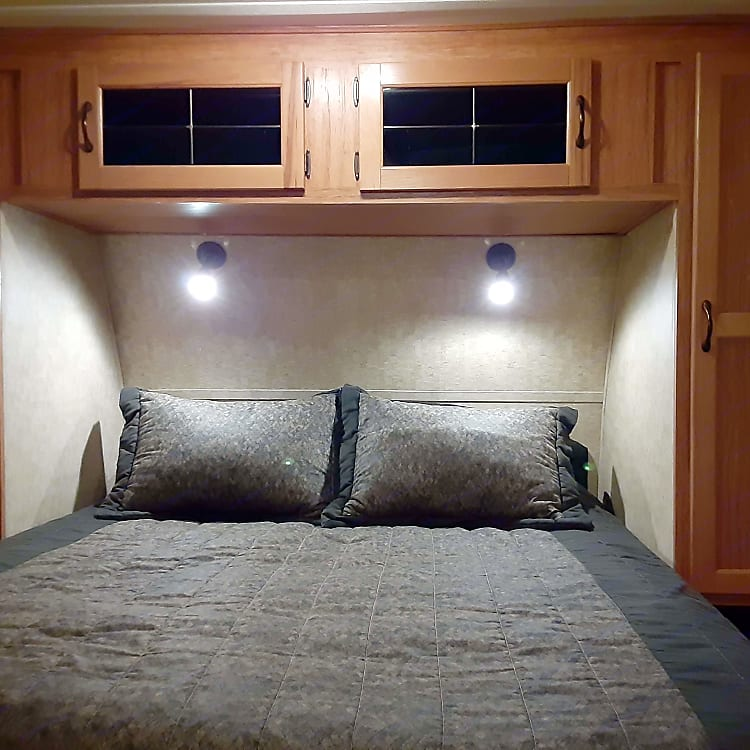 Bedroom with Queen bed and wardrobe closet on each side and overhead storage.