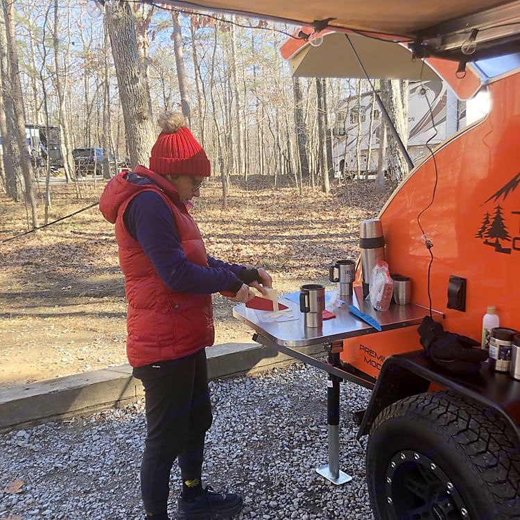 A stainless steel table attaches to the exterior of the camper to provide extra food prep space