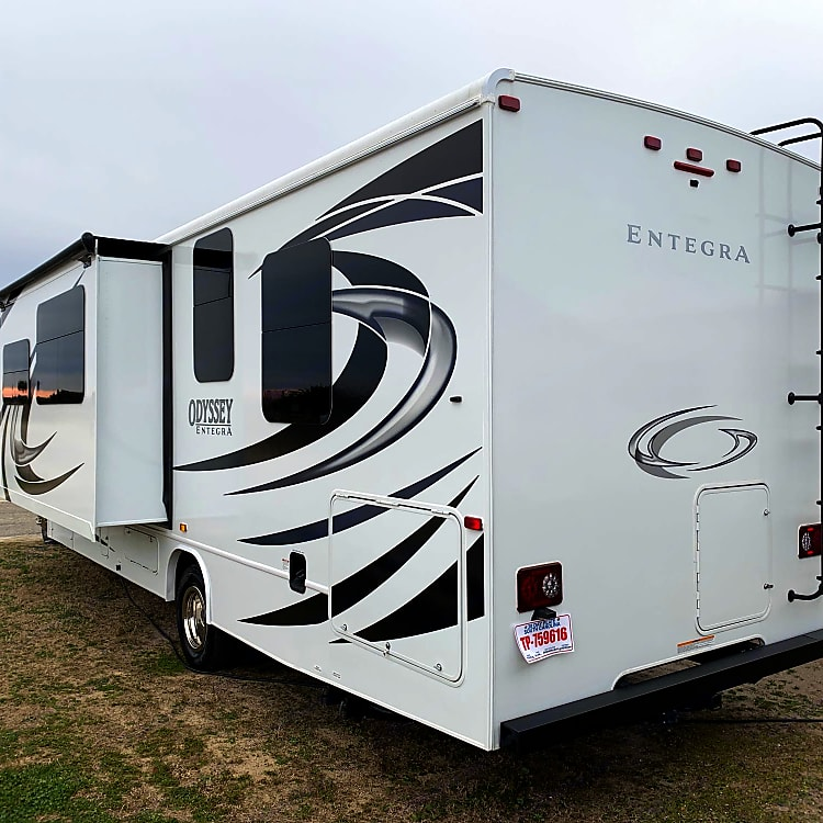"""Outdoor hot/cold shower and built-in water filter.  Slide out, dark tinted windows all around for privacy and temperature management. 4"""" steel rear bumper offers storage for drain tubes, away from your belongings!  Trailer hitch perfect for a bike rack, or tow capacity of 7500 lbs!"""