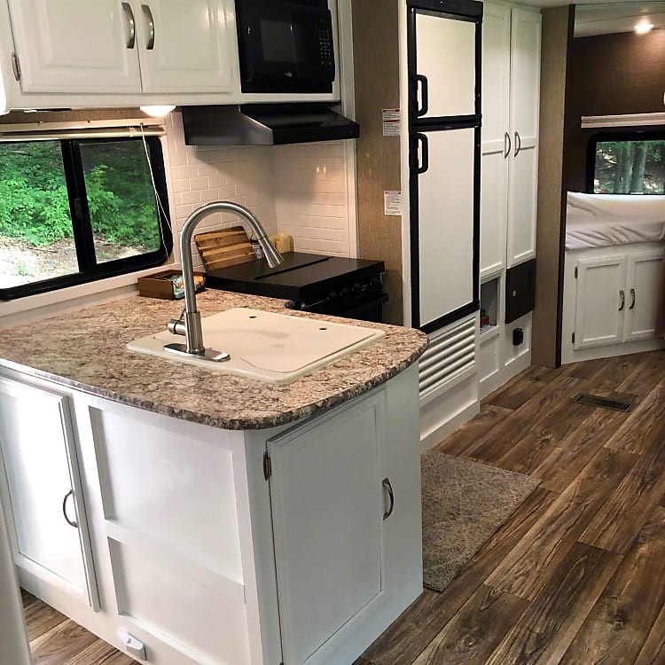 The L-shaped kitchen offers a bigger layout for camper living.  It is fully equipped with pots/pans, flatware, cups, mugs, plates, and bowls. Enjoy!
