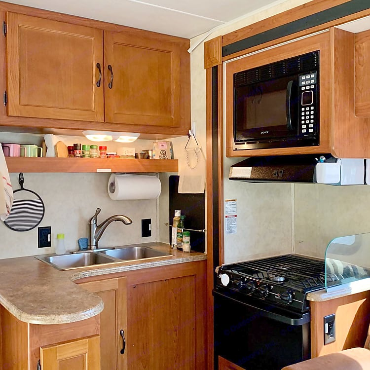 Spacious L-shaped kitchen with 3-burner stove, oven, microwave; nice counter space