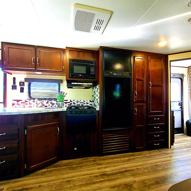 Kitchen with spacious area. Fringe, microwave, sink stove/oven, and plenty of storage.