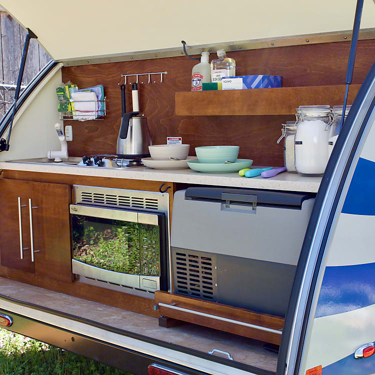 Spacious outdoor kitchen with microwave, fridge, two burner stove, and sink