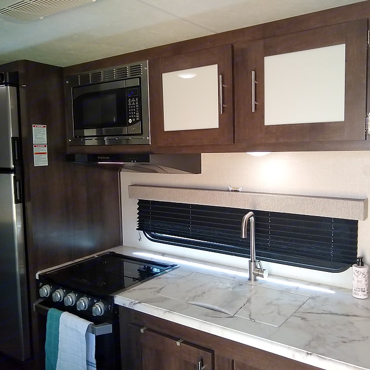 Kitchen has a 3 burner propane stove, an oven, a microwave, fridge with freezer, and a sink.