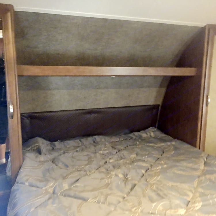 Master bedroom has a queen mattress with hanging storage on each side.