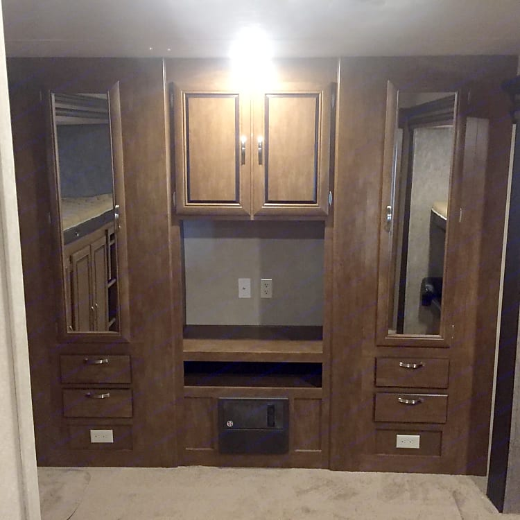 Entertainment center with TV and DVD player.  Some drawers and two hanging storage closets.