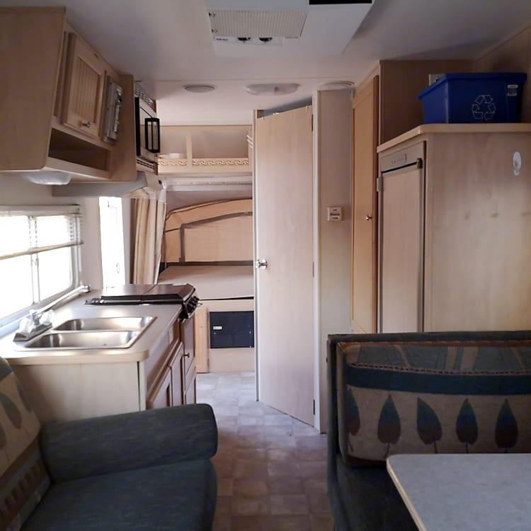 The kitchen, bathroom door, storage cabinet and double bed.