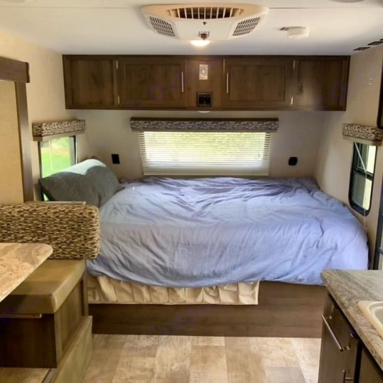 Queen bed in front, many windows, storage cabinets above; shoe storage below, a/c on ceiling