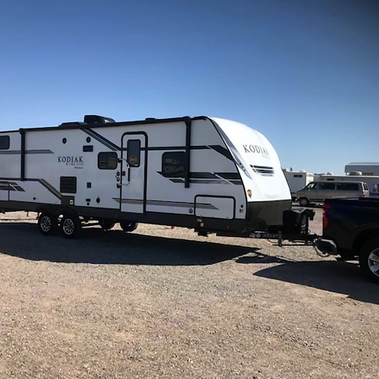 The travel trailer has a small outdoor kitchen with a fridge and a burner. Located at the back of the trailer. Big awning for shade and outdoor shower