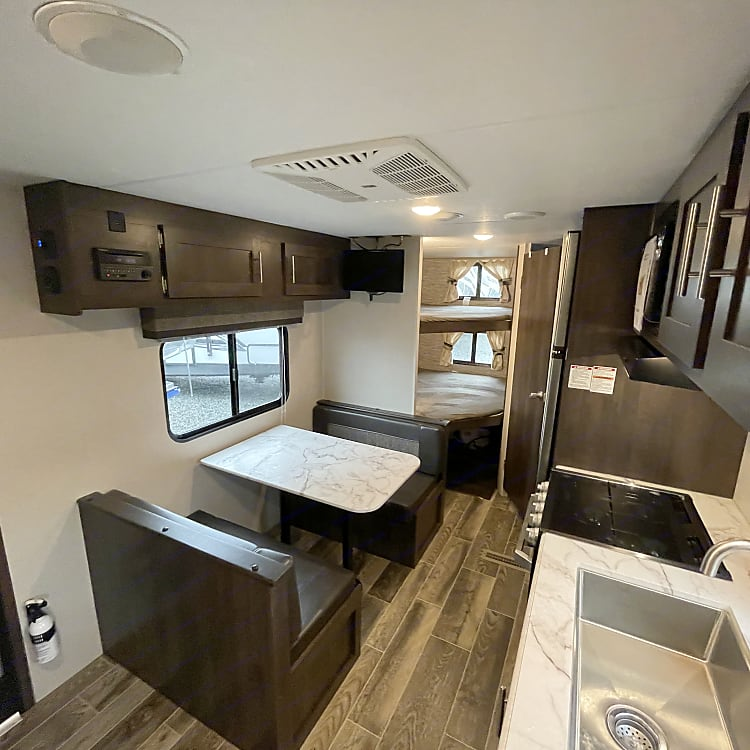 This is a picture from the front of the couch, facing the tv, dining area, full size kitchen, and corner bunks (divided by private wall!)