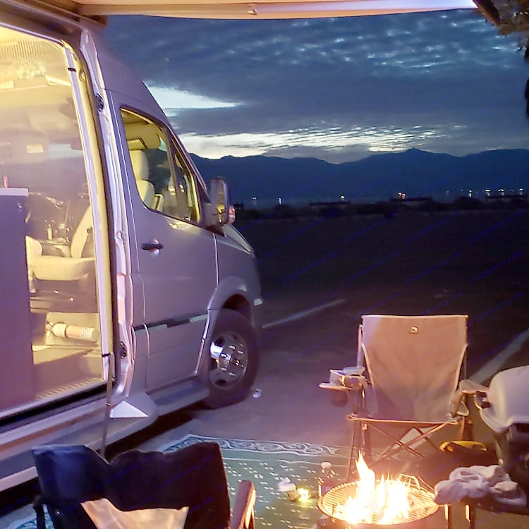 lit awning with propane fire pit, camping chairs and outdoor barbeque.