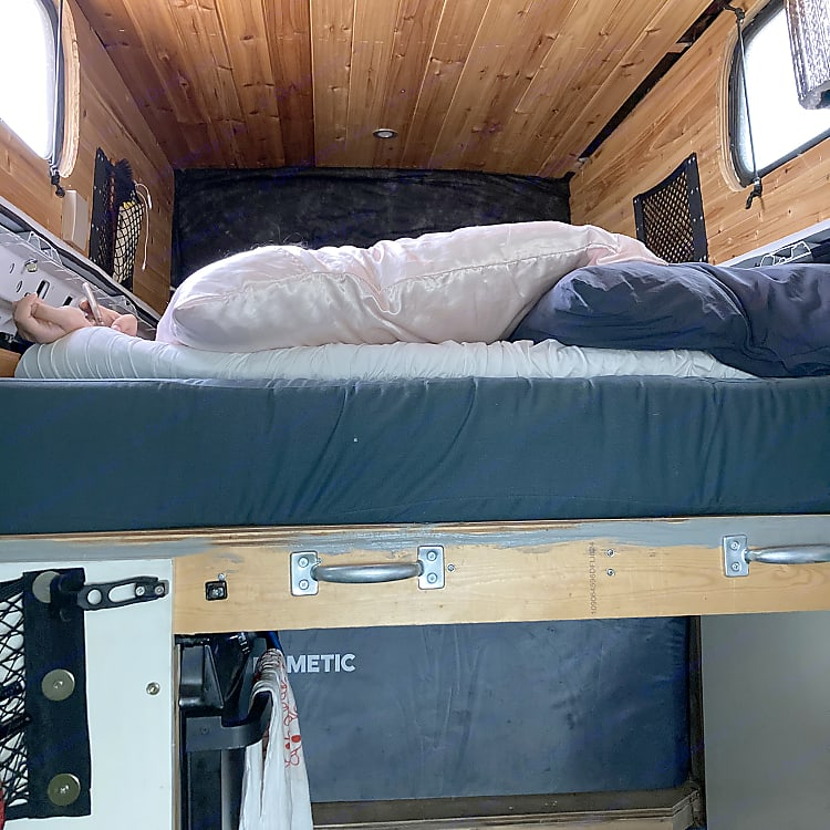 The bed slides out over the fridge, stove, and sink. Three pads lay out over the wood. Super comfortable.
