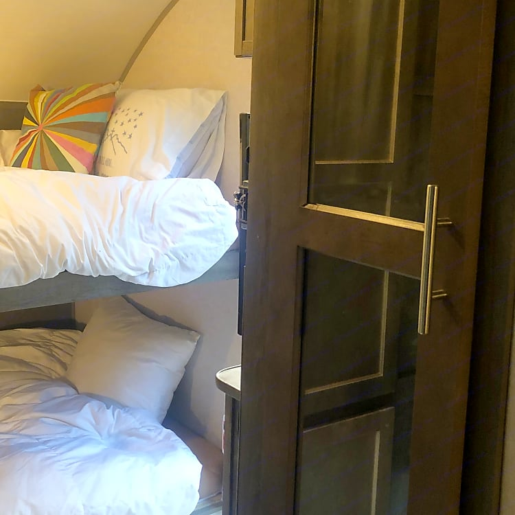 Bunkbeds with feather mattress, larger than a twin & sleep two kids comfortably. Ample storage -- pantry, closet, plus drawers and under bed storage.