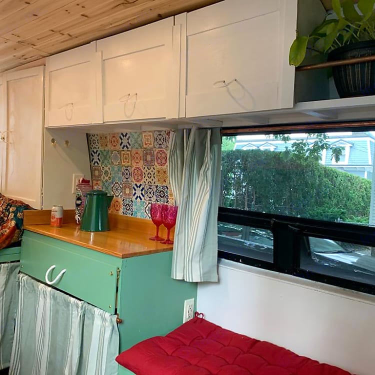 The three upper cabinets hold towels, percolator, bowls and plates, and tea and coffee.