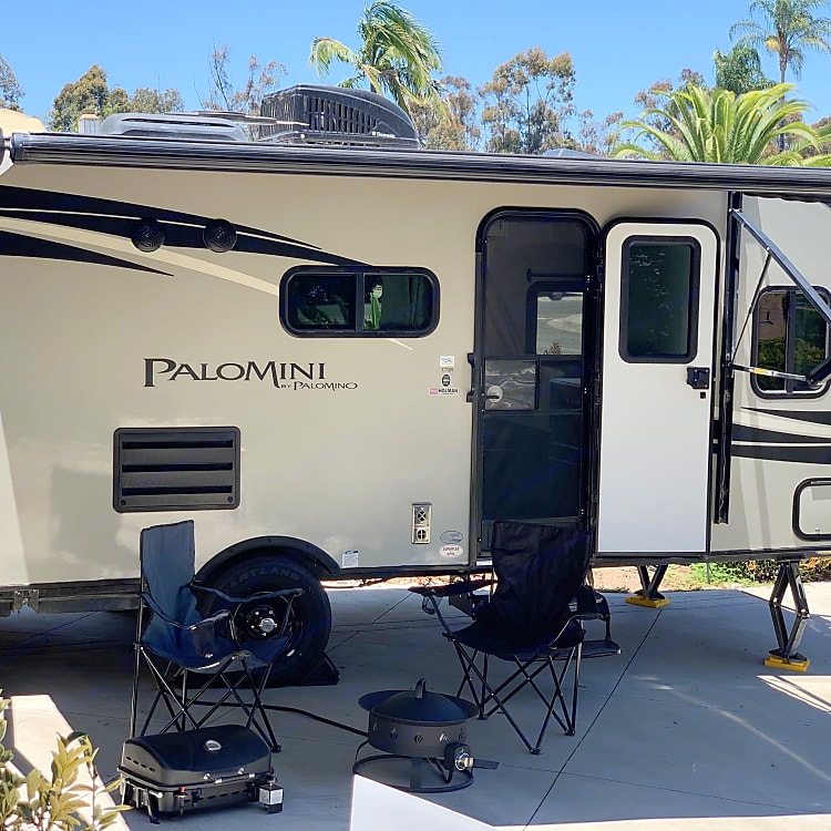 Camping grill, gas fire ring, chairs (3 adult size, 1 child size included), and the spacious, LED-lit awning.