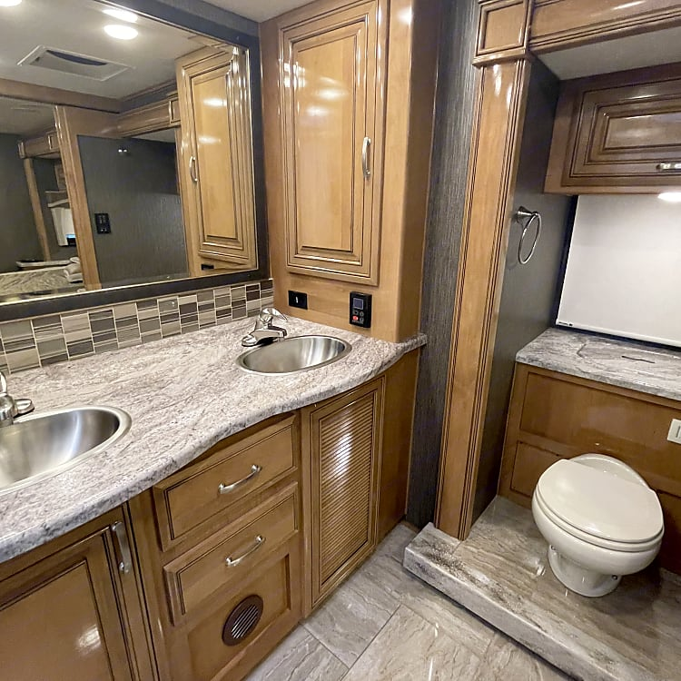 Dual sinks and toilet in the back of the coach.