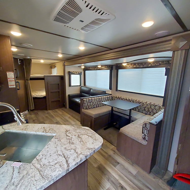 This shows the view from the front door. Here you can see the u-shaped dinette with removable and adjustable table, sofa, and the double bunk beds.