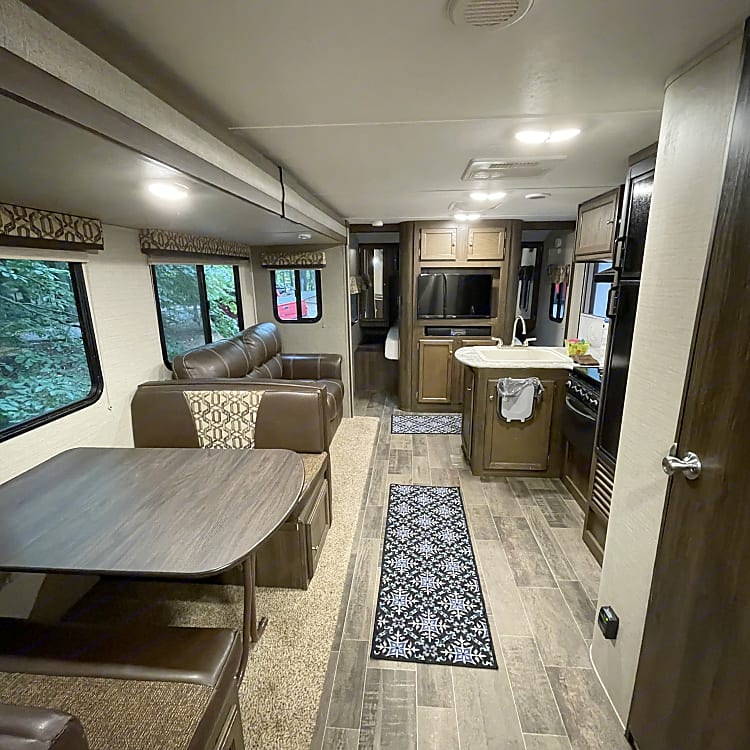 Spacious view from back of the trailer bunk area. Dining room table that converts to bed.