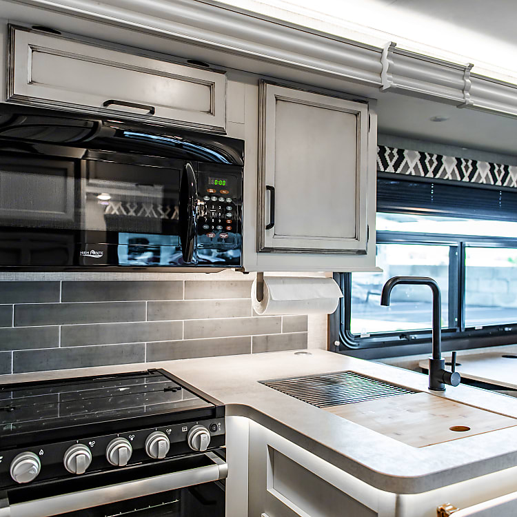 The kitchen has a beautiful farmhouse interior with a 3 burner stove, a small oven, a residential microwave, a beautiful sink and plenty of storage!
