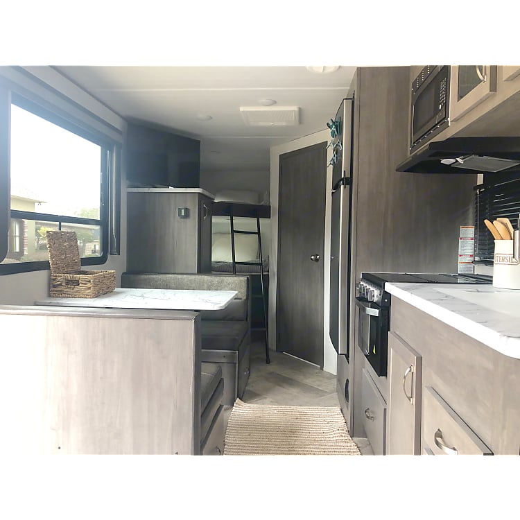 Kitchen with dinette (converts to bed), farmhouse style sink with flexible faucet, full fridge, 3 burner gas stove, and gas oven