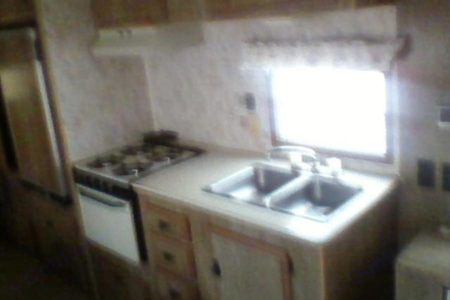 Full kitchen with stove, oven, sink and fridge.