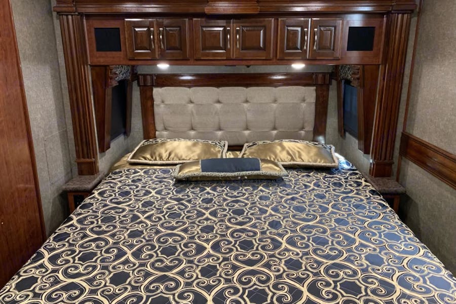 Master king bed with controls for lights, generator, or exterior cameras.