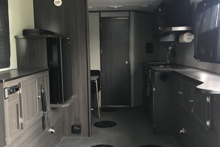 Kitchen with flat screen, oven, stove and sink as well as refrigerator.