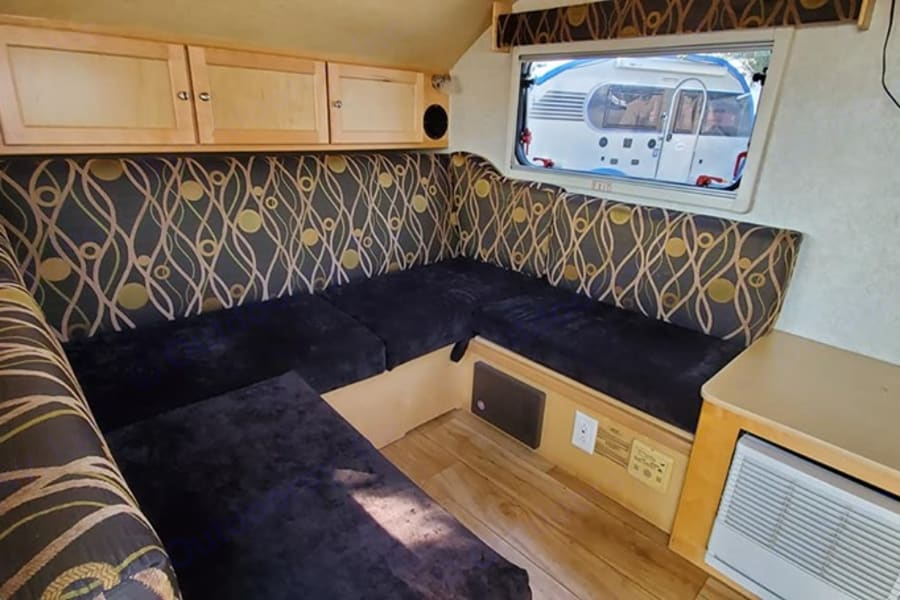 """View from door of seating area.  Cushions pull in and back flops down to make a ~king-sized bed (70 x 73"""")"""