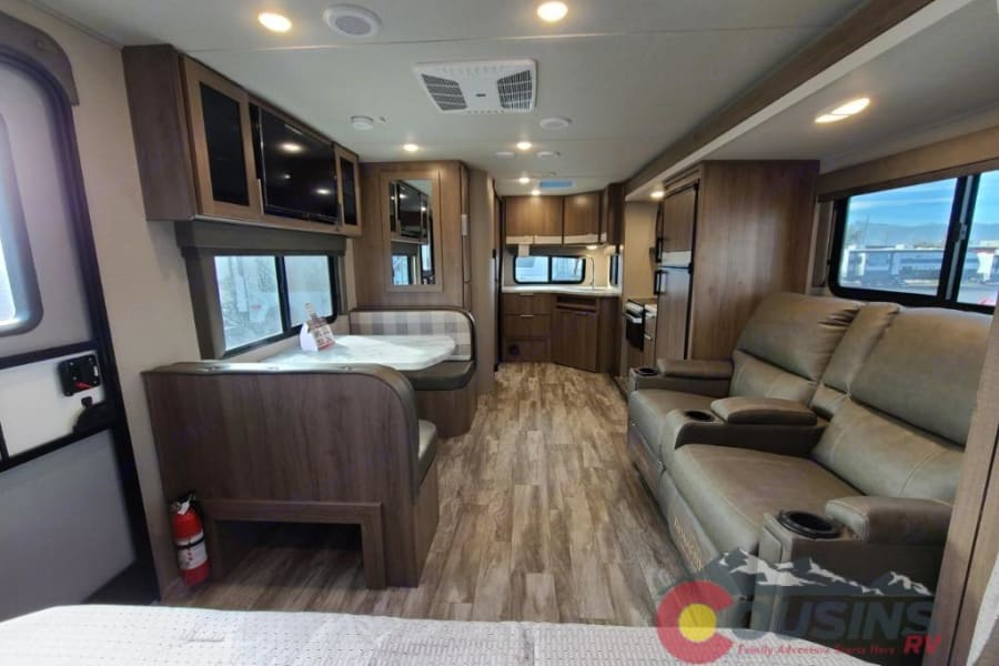 Interior looking toward the back of the camper. Comfy recliners and dinette.