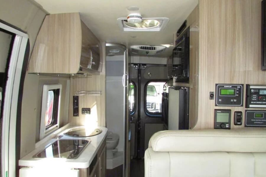 Corian countertops, white leather seats, light wood cabinets and light colored vinyl flooring. Refrigerator and Freezer just behind the dinette seat